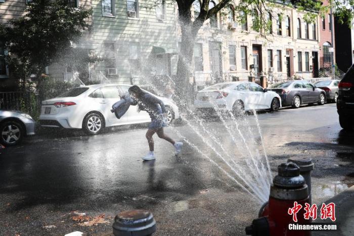 当地时间7月16日,纽约布鲁克林街道上部分消防栓喷水为市民消暑,一名女孩戏水。当日,美国纽约出现36摄氏度高温,纽约市部分街区打开消防栓喷水为市民消暑。 中新社记者 廖攀 摄
