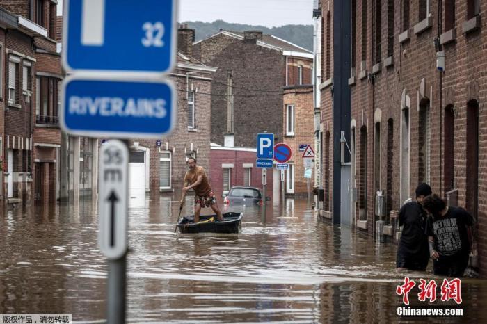 """比利时列日省昂格勒,一名男子在洪水过后沿着居民区划船前行。在比利时,负责整合协调救援行动的国家危机中心指出,死亡人数已攀升至27人,103人仍""""失踪或失联""""。"""