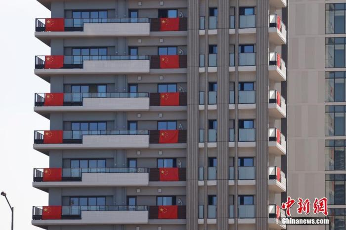 当地时间7月19日,记者探访东京奥运会奥运村广场。图为中国奥运代表团入住的房间阳台悬挂中国国旗。 中新社记者 富田 摄
