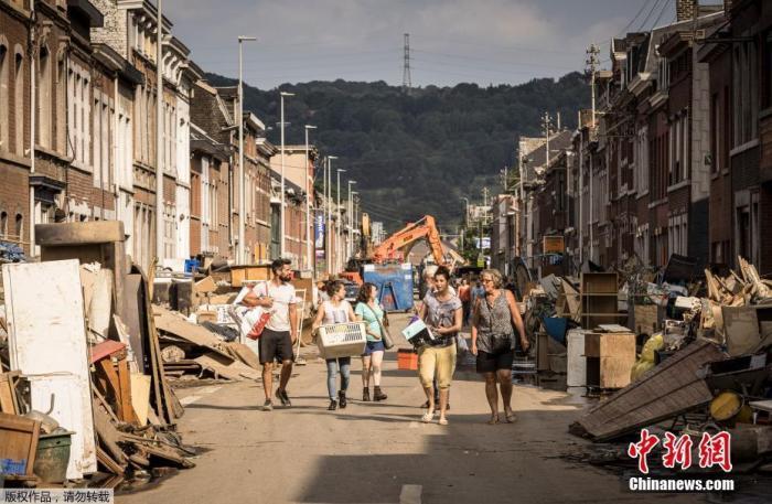 7月20日讯,欧洲中西部地区强降雨引发的洪水尚未完全消退,截至当地时间18日下午至少有187人在洪灾中遇难,其中德国156人、比利时31人。德国莱茵兰-普法尔茨州受灾最为严重,目前已有至少110人死亡。随着搜救行动继续,预计伤亡人数将进一步上升。德国政府网站信息显示,目前约有900名联邦国防军官兵投入救援。图为当地时间2021年7月19日,比利时佩宾斯特,居民们在一条居民携带着家庭物品行走在街上,由于严重洪灾将溪流和街道变成汹涌的洪流,冲走了汽车,导致房屋倒塌。