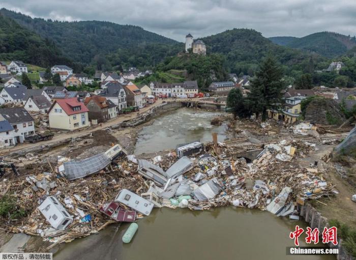 图为当地时间2021年7月19日,德国阿尔特纳尔,商队、油箱、树木和废料堆在Ahr的一座桥上,高达数米。镇上许多房屋被完全摧毁或严重损坏。