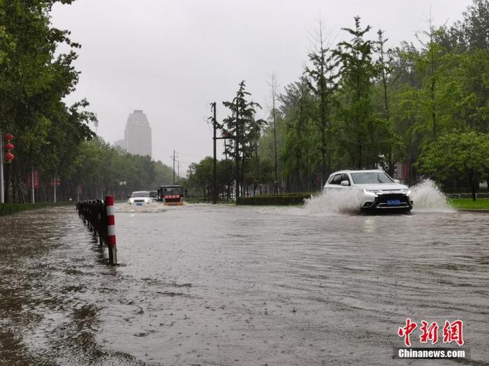 7月20日,河南郑州,车辆从积水路段通过。近日,郑州连遭暴雨袭击,持续强降雨导致部分街头积水严重。 /p中新社记者 李贵刚 摄