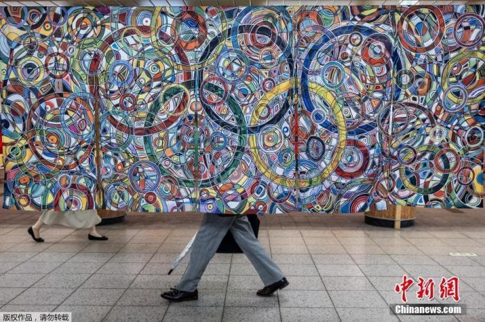 东京街头洋溢奥运气息,图为东京火车站的奥林匹克广场,人们走过前英国奥运标枪运动员罗尔德·布拉德斯托克的画作《奥林匹克之强》。