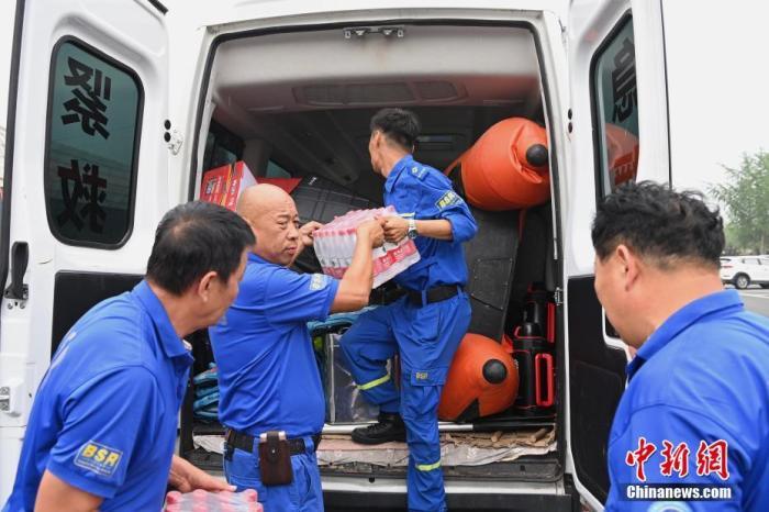 资料图:驰援河南的救援队队员搬运物资。 中新社记者 崔楠 摄