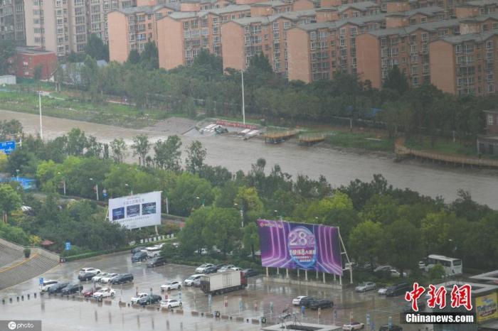 2021年7月21日,河南,郑州暴雨第二日,早上在市区,虽然降雨仍在持续,但昨晚积水路段的积水明显下降,目前公共交通未恢复,市区内部分道路可以正常通行,街上有市民骑车或行走赶路。昨日形成的积水区域被困车辆较多。图片来源:ICphoto