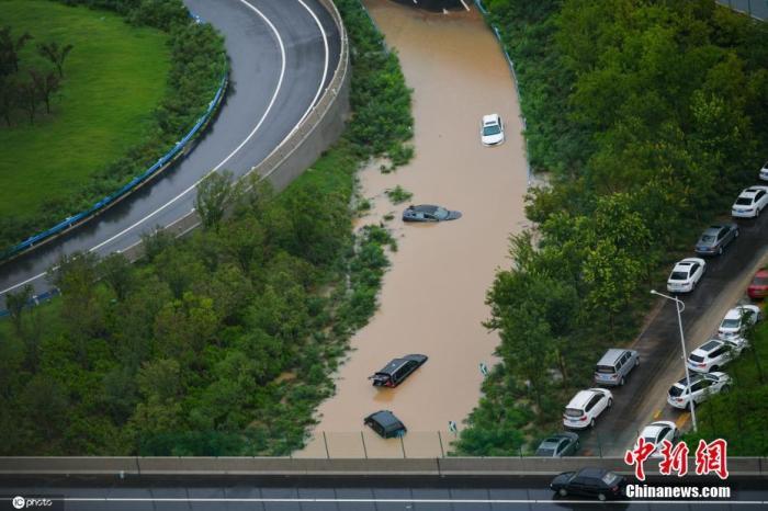 7月21日,河南,郑州暴雨第二日,早上在市区,虽然降雨仍在持续,但昨晚积水路段的积水明显下降,目前公共交通未恢复,市区内部分道路可以正常通行,街上有市民骑车或行走赶路。昨日形成的积水区域被困车辆较多。图片来源:ICphoto