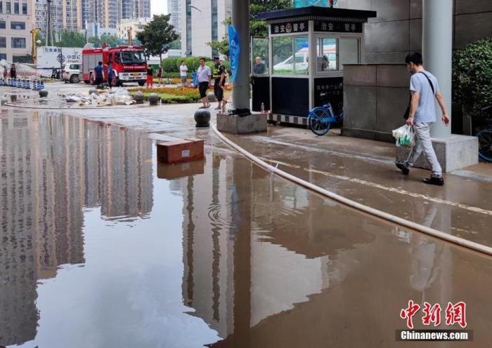 资料图:7月22日,行人经过位于河南省郑州市的郑州大学第一附属医院河医院区的积水路面。受强降雨及院区地势低洼影响,该院受灾严重,后经院方积极应对,全院病患、医护人员已安全转运至其他院区。 <a target='_blank' href='http://www.chinanews.com/'>中新社</a>记者 阚力 摄