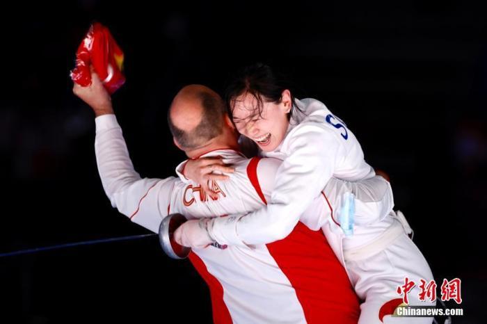 7月24日晚,东京奥运会女子重剑个人赛结束了决赛的较量,中国选手孙一文以11:10战胜罗马尼亚选手波佩斯库,夺得冠军。这是中国体育代表团在本届奥运会的第三枚金牌。图为孙一文夺冠后和团队成员一起庆祝。<a target='_blank' href='http://www.chinanews.com/'>中新社</a>记者 富田 摄
