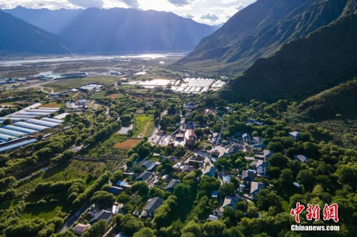 """位于西藏自治区尼洋河畔的林芝嘎拉村,每逢春天,桃花夹岸而开,青稞吐绿、落英缤纷,已成为远近闻名的旅游目的地。上世纪八十年代,嘎拉村村民多在色季拉山山沟里伐木维生。如今风景秀丽的""""桃花源"""",是从当年的伐木村转变而来。图为7月22日傍晚,西藏嘎拉村与远处尼洋河风光。中新社记者 江飞波 摄"""