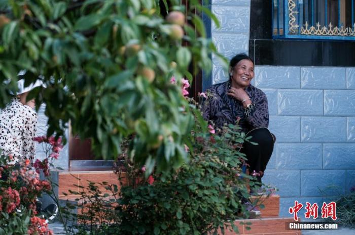 """位于西藏自治区尼洋河畔的林芝嘎拉村,每逢春天,桃花夹岸而开,青稞吐绿、落英缤纷,已成为远近闻名的旅游目的地。上世纪八十年代,嘎拉村村民多在色季拉山山沟里伐木维生。如今风景秀丽的""""桃花源"""",是从当年的伐木村转变而来。图为7月22日,西藏嘎拉村村民卓玛在自家客厅门口闲坐。 中新社记者 江飞波 摄"""