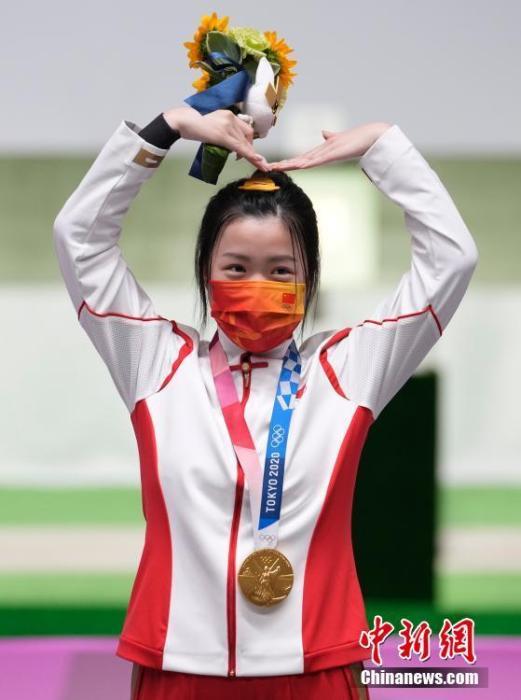7月24日举行的东京奥运会女子10米气步枪决赛中,中国选手杨倩夺得冠军,为中国代表团揽入本届奥运会第一枚金牌。这也是本届东京奥运会诞生的首枚金牌。图为杨倩在领奖台上比出爱心手势。<a target='_blank' href='http://www.orbitpk.com/'>中新社</a>记者 杜洋 摄
