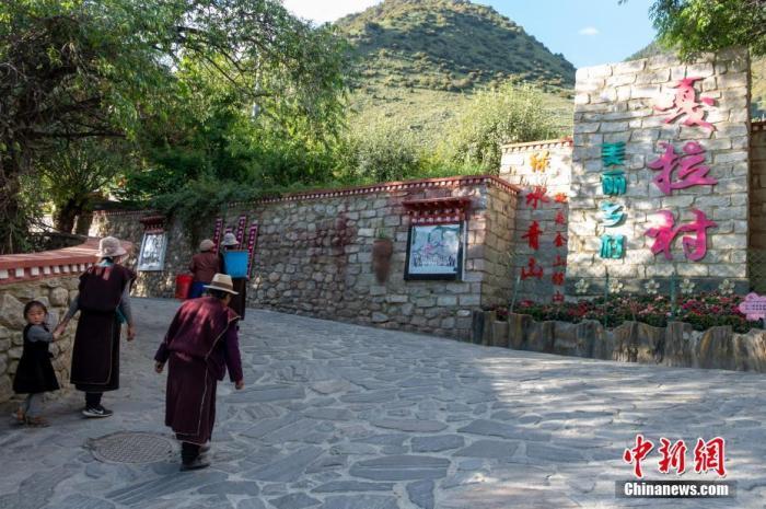 """位于西藏自治区尼洋河畔的林芝嘎拉村,每逢春天,桃花夹岸而开,青稞吐绿、落英缤纷,已成为远近闻名的旅游目的地。上世纪八十年代,嘎拉村村民多在色季拉山山沟里伐木维生。如今风景秀丽的""""桃花源"""",是从当年的伐木村转变而来。图为7月22日,嘎拉村村民路过村口,村里干净整洁,""""绿水青山就是金山银山""""的理念深入人心。 中新社记者 江飞波 摄"""