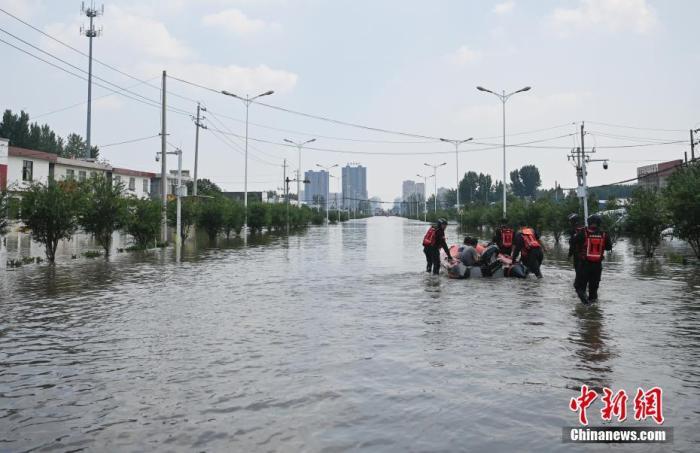 资料图:救援人员转移受灾民众。 中新社记者 崔楠 摄