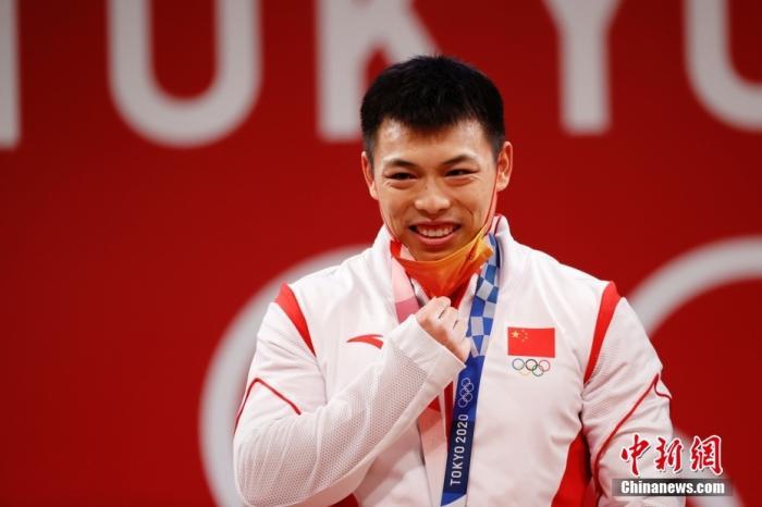 北京时间7月25日晚,在东京奥运会男子举重67公斤级比赛中,中国选手谌利军以抓举145公斤、挺举187公斤、总成绩332公斤夺冠,打破挺举和总成绩奥运纪录的同时,也为中国体育代表团摘得本届奥运会的第六金。图为谌利军在颁奖仪式上摘下口罩。 <a target='_blank' href='http://www.chinanews.com/'>中新社</a>记者 韩海丹 摄