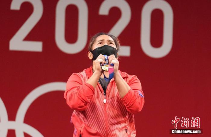 7月26日,菲律宾选手迪亚兹手捧金牌。当日,东京奥运会举重女子55公斤级比赛在东京国际论坛大厦举行。菲律宾选手迪亚兹获得冠军。这也是菲律宾获得有史以来第一块奥运金牌。 <a target='_blank' href='http://www.orbitpk.com/'>中新社</a>记者 杜洋 摄