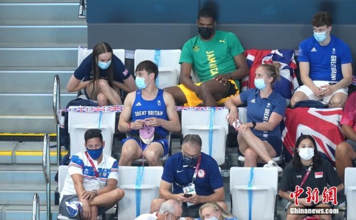 当地时间8月1日,东京奥运会女子单人3米板决赛现场,此前夺得男双10米台冠军的英国名将戴利边看比赛的同时还在织毛衣。图片来源:视觉中国