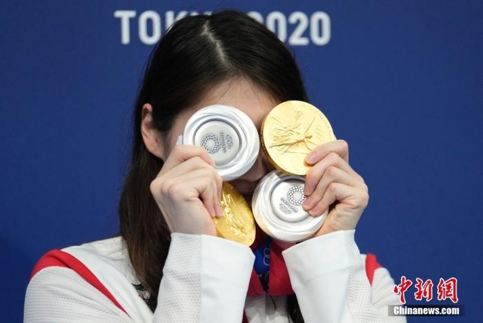 """当地时间8月1日,东京奥运会游泳比赛全部结束,张雨霏在游泳馆展示自己的四块奖牌,拍照留念。本届奥运会,张雨霏游了12枪共收获了2金2银,是当之无愧的""""劳模""""。中新社记者 杜洋 摄"""