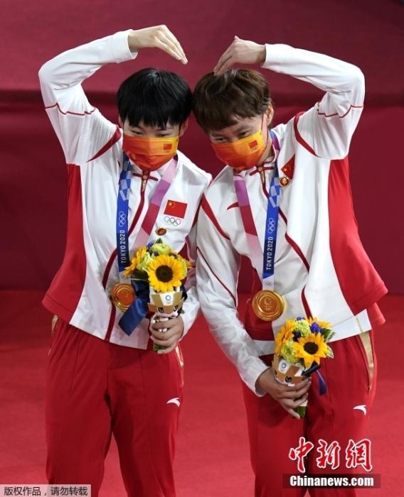 北京时间8月2日,在东京奥运会场地自行车女子团体争先赛中,由钟天使和鲍珊菊组成的中国队以31秒895夺得冠军。这是中国代表团的第28金。图为钟天使(右)和鲍珊菊(左)比心。