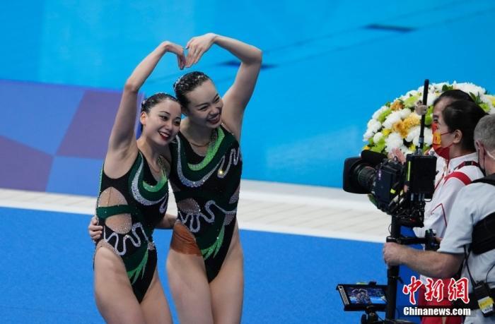 8月4日晚,东京奥运会花样游泳双人自由自选决赛进行,中国组合黄雪辰/孙文雁得到96.9000分,加上此前的技术自选得分,最终她们以192.4499分夺得亚军,俄罗斯奥运组合夺得冠军。图为赛后中国组合面对镜头比心。 /p中新社记者 杜洋 摄