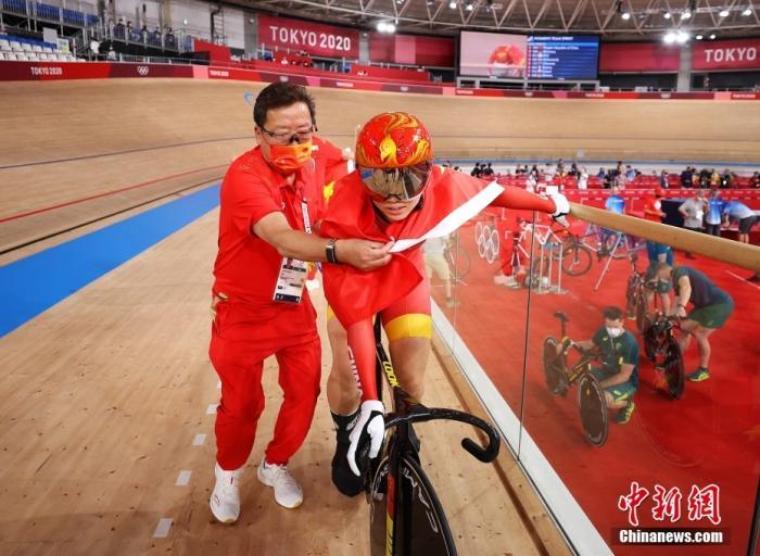 当地时间8月2日,场地自行车女子团体争先赛,钟天使和鲍珊菊组成的中国队击败对手,夺得金牌。图为教练为鲍珊菊披上国旗。图片来源:视觉中国