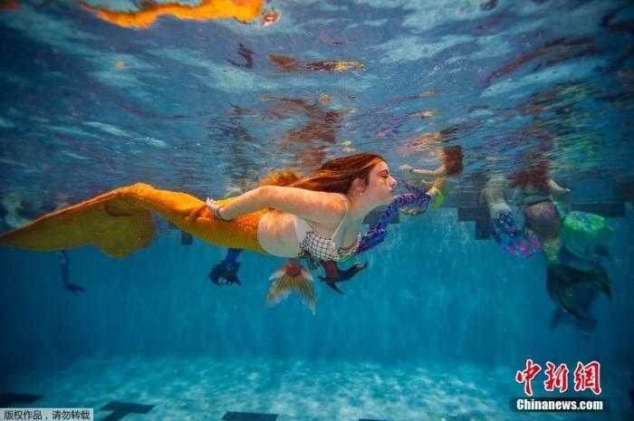 """当地时间8月7日,美国弗吉尼亚州马纳萨斯,""""美人鱼""""参加MerMagic Con的拍照活动。MerMagic Con被宣传为世界规模最大的""""美人鱼大会""""。大会的多数参与者是模特,看起来就像美国""""美人鱼""""小姐选美大赛。而胖美人鱼协会则希望把肥胖人士聚集在一起,宣扬任何人都可以成为美人鱼的理念。"""