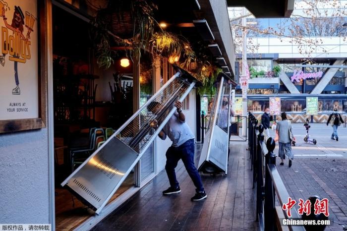 资料图:澳大利亚首都堪培拉,酒吧的工作人员正在将户外设施收回店内。