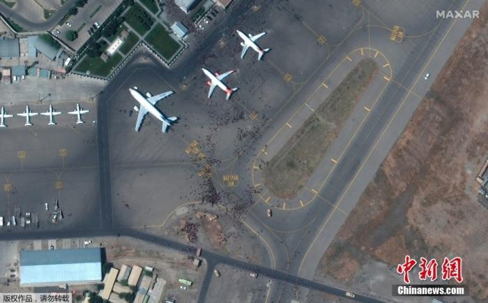 """当地时间8月16日,阿富汗喀布尔国际机场,卫星照片显示机场停机坪上人群密集。阿富汗塔利班当天进入首都喀布尔,宣布""""战争已经结束""""。美国等西方国家外交人员、大批阿富汗民众,涌向喀布尔机场准备撤离,导致机场秩序混乱。"""
