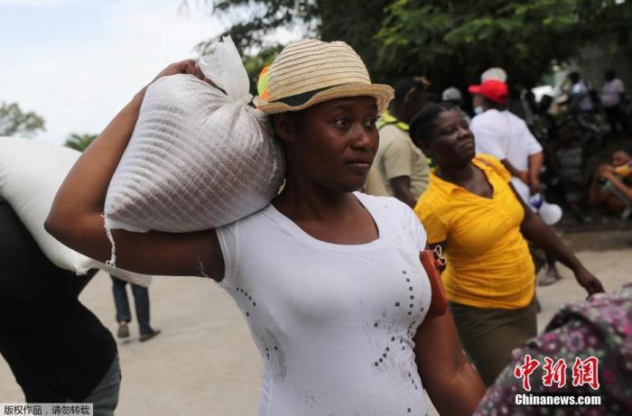 当地时间8月19日,海地南部,民众排队领取世界粮食计划署援助的物资。