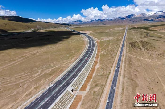 8月21日,据西藏自治区交通运输厅介绍,当日,G6京藏高速公路那曲至羊八井段通车试运行。至此,全长295公里的G6京藏高速公路那曲至拉萨段(简称那拉高速公路)全线通车,这是当前世界海拔最高的高速公路。资料图为6月28日,即将通车的西藏那拉高速公路,画面右侧为著名的青藏公路。(无人机画面) 中新社记者 江飞波 摄