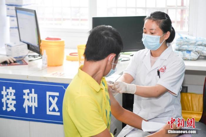 资料图:医务人员为接种者打新冠疫苗。杨华峰 摄