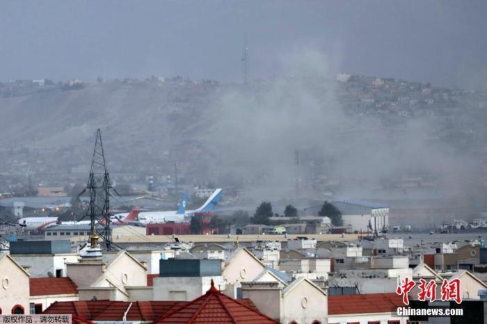 """当地时间8月26日,阿富汗首都喀布尔机场外发生两起爆炸,导致至少60名阿富汗人和13名美军身亡。极端组织""""伊斯兰国""""宣布对此次事件负责。图为喀布尔国际机场外当天发生爆炸,现场浓烟滚滚。"""