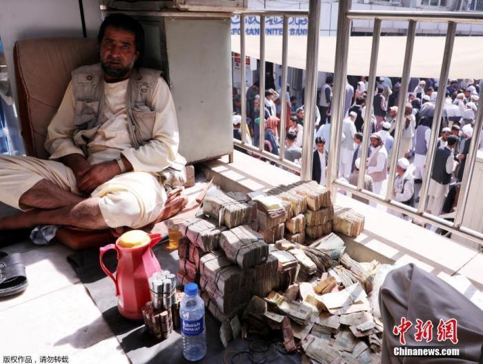 当地时间9月4日,阿富汗喀布尔,在阿富汗塔利班接管后,银行和市场重新开放,一名货币兑换商在货币兑换市场等待客人。