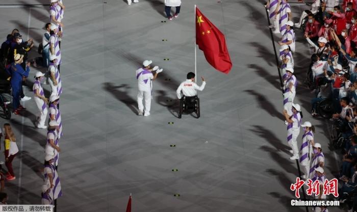 9月5日,第16届夏季残疾人奥运会闭幕式在日本东京举行。图为中国代表团旗手、女子轮椅篮球运动员张雪梅持五星红旗进入体育场。