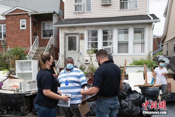 当地时间9月5日,美国纽约市皇后区受飓风洪水袭击的房屋前,相关工作人员统计受灾情况。记者 廖攀 摄