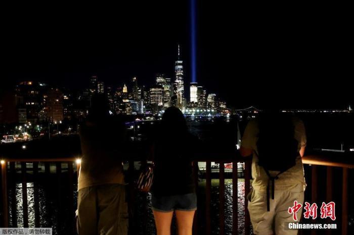 """当地时间9月10日,美国纽约,纽约""""纪念光柱""""亮灯,纪念 """"9·11""""事件20周年。图为民众观看""""纪念光柱""""。"""