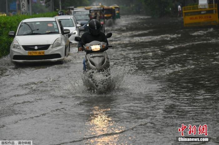 当地时间9月11日,印度新德里,一场暴雨过后路面积水严重,民众骑摩托车经过充满积水的道路。