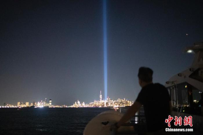 """当地时间9月10日夜间,从美国纽约哈德逊河上航行的轮船上眺望曼哈顿,两根象征世贸中心双子塔的蓝色光柱正在进行测试。天明后,纽约将迎来""""9·11""""事件20周年纪念日。 记者 廖攀 摄"""