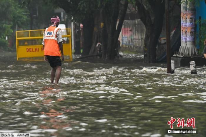 资料图:当地时间9月11日,印度新德里,一场暴雨过后路面积水严重,市政工人正在疏通排水设施。