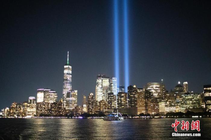 """当地时间9月10日夜间,从美国纽约哈德逊河上航行的轮船上眺望曼哈顿,两根象征世贸中心双子塔的蓝色光柱正在进行测试。天明后,纽约将迎来""""9·11""""事件20周年纪念日。 <a target='_blank' href='http://www.leachink.com/'>中新社</a>记者 廖攀 摄"""