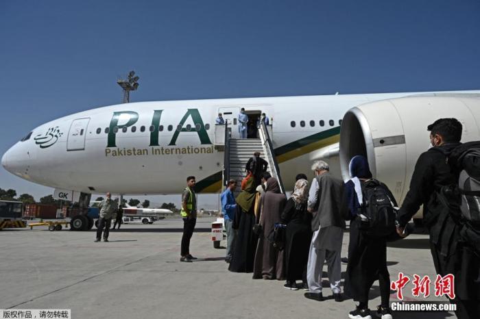 资料图:当地时间9月13日,阿富汗喀布尔机场,乘客登上巴基斯坦国际航空公司的航班。据报道,这是自阿富汗塔利班8月15日重新接管喀布尔以来,首个降落的国际商业航班。