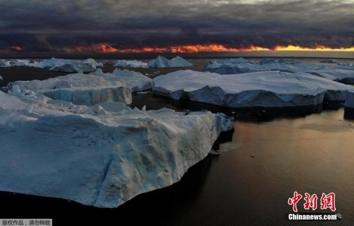 当地时间9月14日,格陵兰岛伊卢利萨特附近的迪斯科湾,日落时,阳光反射在冰山上,画面静谧美好。
