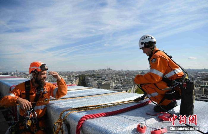闻名世界的巴黎地标凯旋门被包裹起来,引发全球瞩目。包裹项目工程当地时间9月16日已基本完工,施工人员正在进行最后的技术处理。图为施工人员在凯旋门顶部作业。 中新社记者 李洋 摄