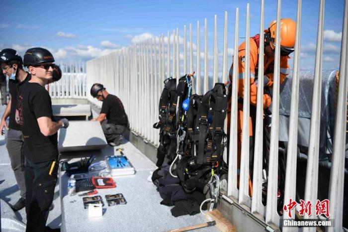 图为施工人员在凯旋门顶部作业。 中新社记者 李洋 摄