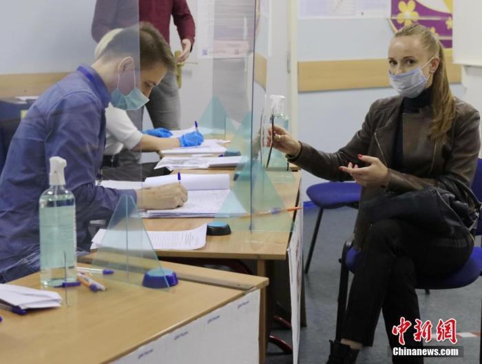当地时间9月17日,一名选民在投票站内向工作人员出示身份信息。俄罗斯第8届国家杜马(议会下院)选举以及39个地方议会和9个联邦主体首脑选举当天举行。 中新社记者 王修君 摄