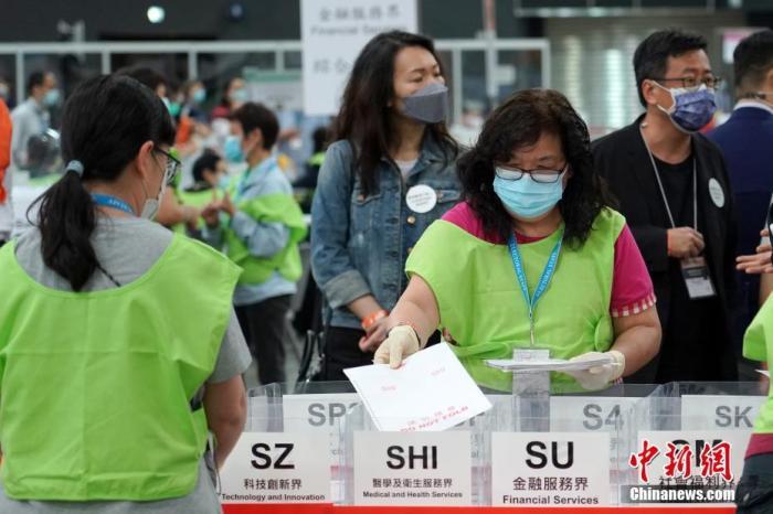 9月20日清晨,2021年香港特区选举委员会界别分组一般选举结果揭晓,412名候选人竞逐的13个界别分组中364席选委全部顺利产生。图为中央点票站工作人员将选票按照13个界别进行分类。 记者 张炜 摄
