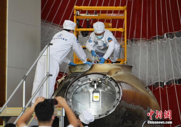 图为工作人员开舱取出搭载物品。 中新社记者 赵隽 摄