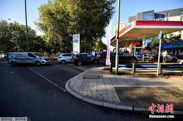 """当地时间2021年9月29日,英国伦敦,民众持续排队加油,不少加油站已经无油可加。由于运油卡车司机短缺,汽油、柴油等燃油难以及时运至加油站,导致英国各地加油站上周开始出现""""油荒""""。"""