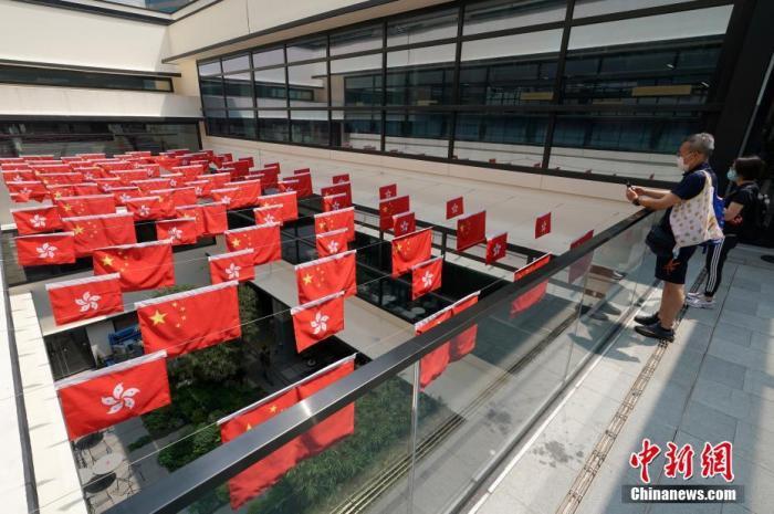 9月30日,国庆节将至,香港街头充满喜庆气氛,活化后重新开业的中环街市挂满五星红旗和香港区旗,吸引市民打卡拍照。 <a target='_blank' href='http://forskolinfuelextract.com/'>中新社</a>记者 张炜 摄