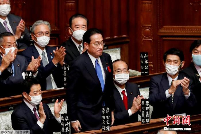 当地时间10月4日,日本自民党总裁岸田文雄经过众院全体会议的首相指名选举成为第100任首相。图为岸田文雄(中)起身致谢。