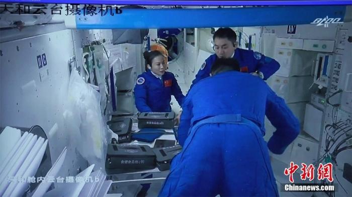 北京时间10月17日9时50分,神舟十三号航天员乘组成功开启货物舱舱门,并顺利进入天舟三号货运飞船对货船内的物品进行核对整理。(视频截图)图片来源:视觉中国